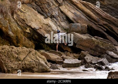 Man is climbing on the rocks of a cliff on the beach during low tide. The cove is surrounded by high cliffs with colorful striations in the rock. - Stock Photo