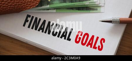 Financial goals written on page of copybook and 100 Euro bills put on it . Business and career big salary saving and investment concept. - Stock Photo