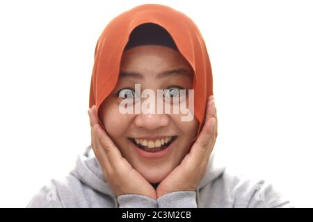 Young Asian muslim woman wearing hijab with surprised excited happy screaming. Cheerful girl with funny joyful face expression, hands holding face, is - Stock Photo