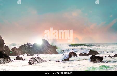Amazing shot of a rocky beach with waves splashes after hitting rocks - Stock Photo
