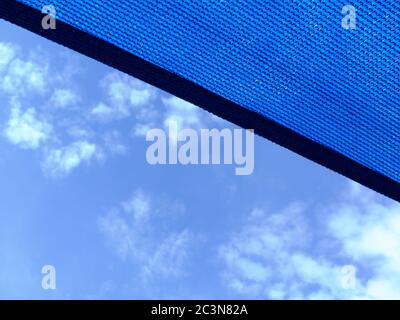 loosely weaved fabric parasol awning. blue sky with clouds. sunny summer day. sun and UV exposure protection concept. medium blue sun proof fabric. - Stock Photo