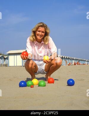 Young woman playing boule game on beach, Lido di Jesolo, Venice Province, Veneto Region, Italy