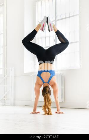 Back view of a woman doing a handstand in a gym bending her legs with feet together in a low angle view in a high key gym in a health and fitness conc - Stock Photo