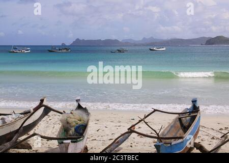 Small jukung boats and breaking wave in Lombok. Kuta Lombok is an exotic paradise on the Indonesian island, with beautiful white sand beaches and crys - Stock Photo