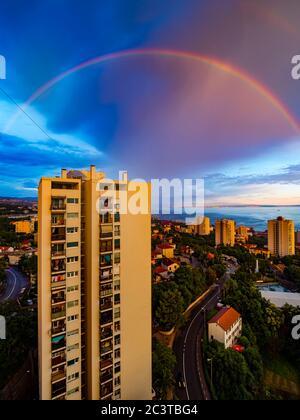 Evening full arc arch rainbow above skyscraper house building - Stock Photo
