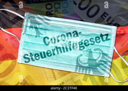 PHOTOMONTAGE, mouth guard with lettering corona control Welfare Act on Germany flag, FOTOMONTAGE, Mundschutz mit Schriftzug Corona-Steuerhilfegesetz a - Stock Photo