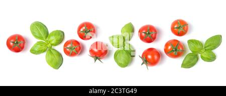 Beautiful border made of fresh red ripe cherry tomatoes with green basil leaves, isolated on white background, vegetable pattern, top view