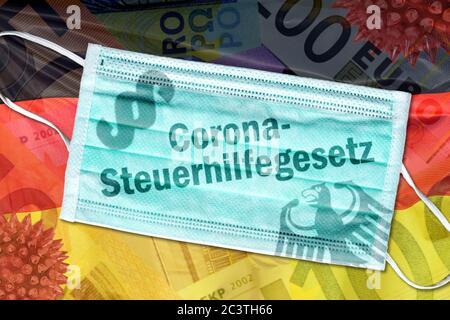 PHOTOMONTAGE, mouth guard with inscription corona Tax Act on Germany flag, FOTOMONTAGE, Mundschutz mit Aufschrift Corona-Steuergesetz auf Deutschlandf - Stock Photo