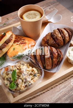 Disposable tableware, lemon tea, slate, mouth-watering sausage rolls and dill and baked potatoes with meat on a wooden tray. Side view.