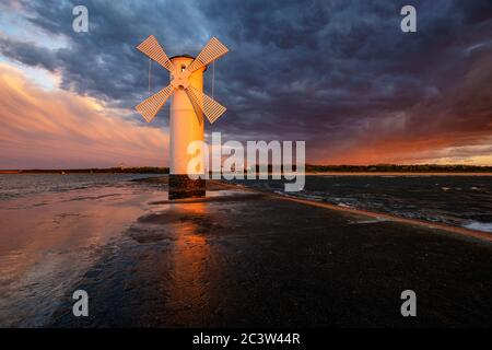 lighthouse in the shape of a windmill in Swinoujscie in Poland during the dramatic sunset - Stock Photo