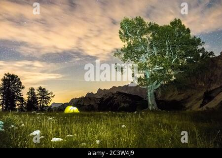 A tent glows under a star night sky at twilight hour. Julian Alps, Triglav National Park, Slovenia, Mountain Slemenova, Sleme. - Stock Photo