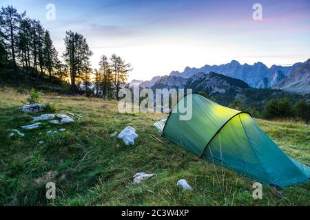 A tent glows under a moon night sky at twilight hour. Julian Alps, Triglav National Park, Slovenia. - Stock Photo