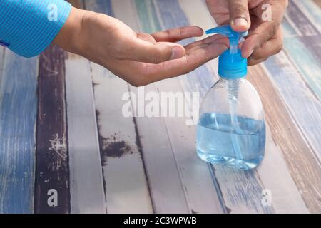 man's hands using hand sanitizer gel, close up - Stock Photo