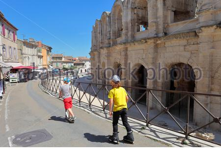 ARLES, FRANCE - JULY 12, 2019: two boys skate near the Arles Amphitheatre; the building testifies to the ancient Roman domination in Provence - Stock Photo