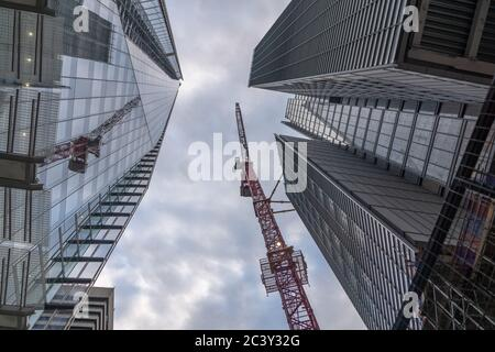 Tall building crane between the glass facades of two even taller skyscrapers - Stock Photo