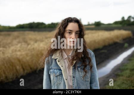 Russia, Omsk, Portrait of young woman with brown hair standing in field - Stock Photo