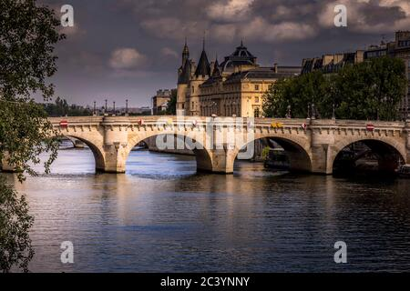 Paris, France - June 9, 2020: Nice view of Pont Neuf bridge and Conciergerie in background on a stormy end of the day in Paris - Stock Photo