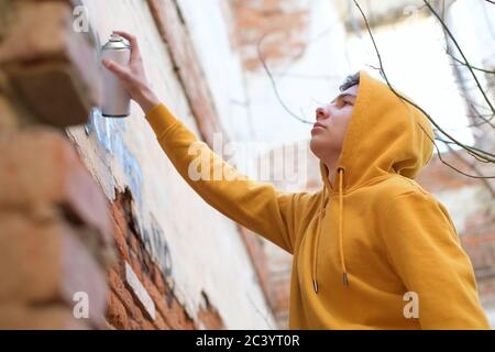 A teenager holds a spray can in his hand and puts inscriptions on the wall - Stock Photo