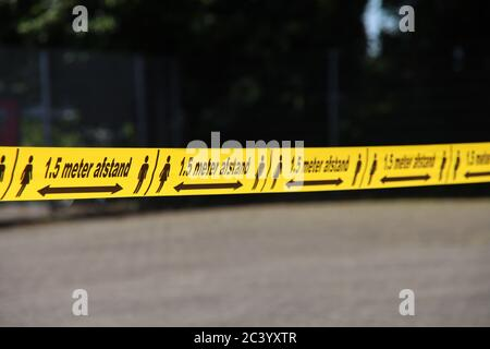 Plastic yellow tape with in dutch language 1,5 meter Afstand to keep people on distance due to the corona covid-19 crisis - Stock Photo