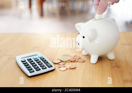 Hand is putting one Euro into a white piggy bank on a table with more coins and a calculator, economy concept for calculate finances and save househol