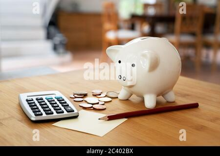 Economy concept, calculator with coins, pencil and a piggy bank on a table in the living room, calculating finances and saving household money, copy s
