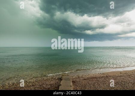 Severe weather with thunderstorms, heavy rain showers and strong winds develop rapidly at Desenzano del Garda city, lake Garda, Brescia, Lombardy, Ita Stock Photo