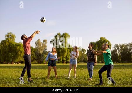 Happy friends playing volleyball game in countryside on summer day. Group of students having fun together outdoors - Stock Photo