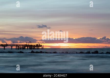 Angler während des Sonnenuntergang auf einer Seebrücke an der Ostsee - Stock Photo