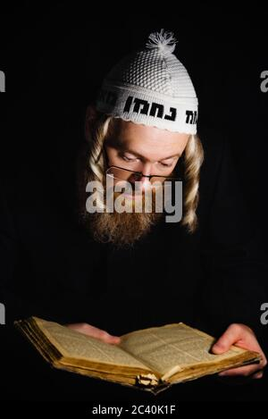 Hasidic jew reading Torah. Religious orthodox jew with sidelocks and red beard in white bale praying in the dark. Low key photo. Vertical orientation - Stock Photo