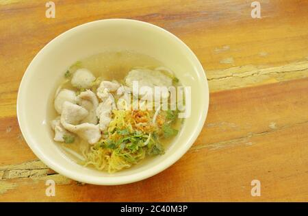 Chinese egg noodles topping slice pork and ball in clear soup - Stock Photo