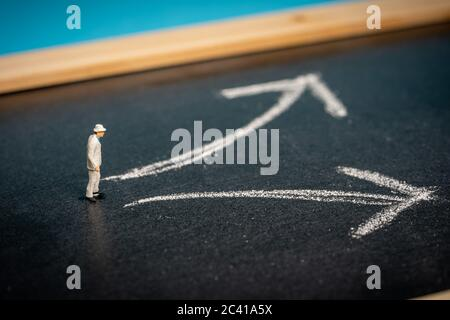 Business concept: Decision making. Miniature man on chalkboard with two arrows pointing at different directions - Stock Photo