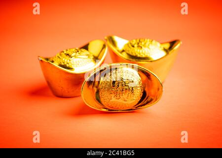 """Chinese gold bars against red background. The wordings on bar is chinese words which means """"bring in wealth and treasure"""""""