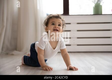 Portrait cute toddler African American girl crawling on wooden floor