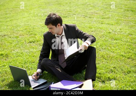 Businessman sitting on the lawn and using a laptop - Stock Photo