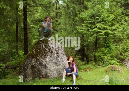 Young man crouches on a rock using binoculars, young woman sitting in the grass - Stock Photo