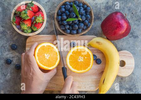 Lady cutting orange on wooden board with multi fruit frome top view.