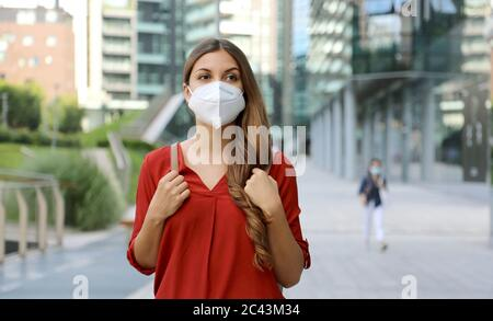 Young woman wearing protective mask KN95 FFP2 walking in modern city street. Student girl with face mask against Coronavirus Disease 2019 (COVID-19). Stock Photo