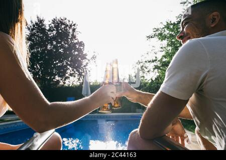 Young couple toasting beer bottle while sitting at poolside - Stock Photo