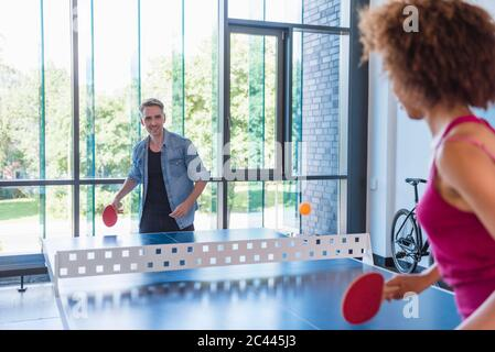 Young business people plaing table tennis in loft office - Stock Photo