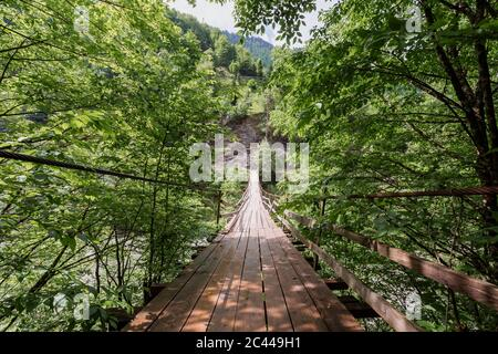 Georgia, Wooden suspension bridge stretching over river - Stock Photo