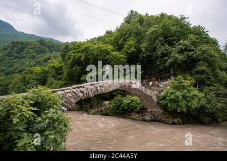Georgia, Adjara, Makhuntseti, Young man crossing stone arch bridge stretching over brown river - Stock Photo