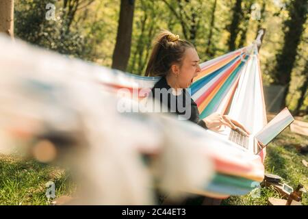 Young woman yawning while using laptop on hammock at yard
