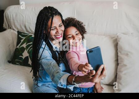 Portrait of happy mother and her little daughter taking selfie with smartphone on the couch