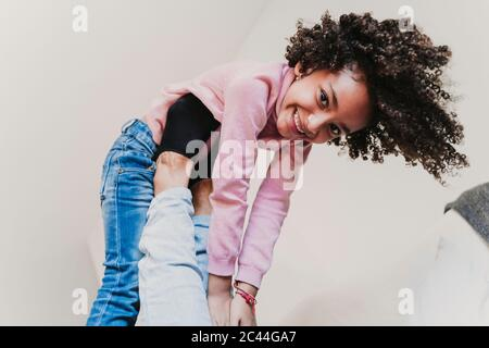 Portrait of happy little girl playing with her mother at home - Stock Photo