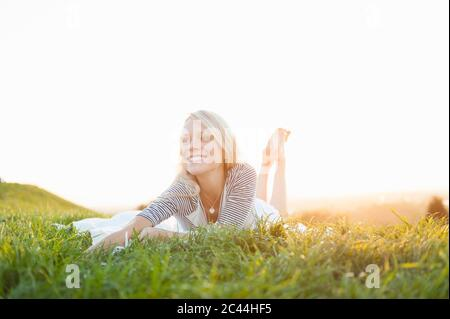 Happy thoughtful young woman lying on grassy land against clear sky in park during sunset