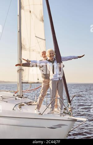 Against the wind. Happy senior couple standing on the side of sail boat or yacht deck floating in sea. Man and woman stretching hands out against the