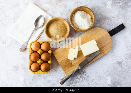 Napkin, spoon, bowls of flour and brown sugar, chicken eggs, cutting board, butter and table knife - Stock Photo