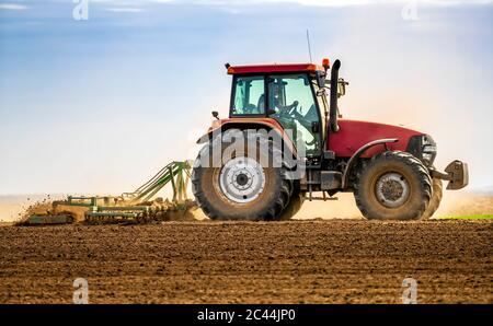 Farmer in tractor plowing field in spring - Stock Photo