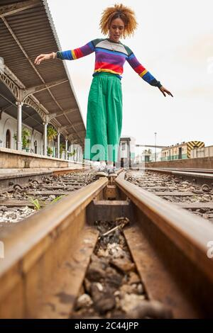 Surface level view of young woman walking on railroad tracks against sky