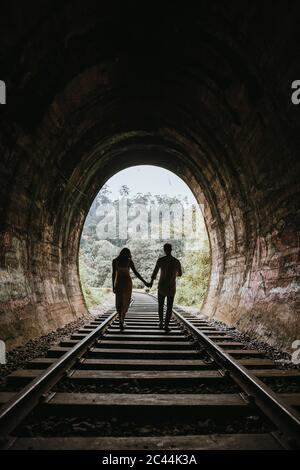 Sri Lanka, Uva Province, Demodara, Silhouette of couple holding hands while walking down tunnel leading to Nine Arch Bridge